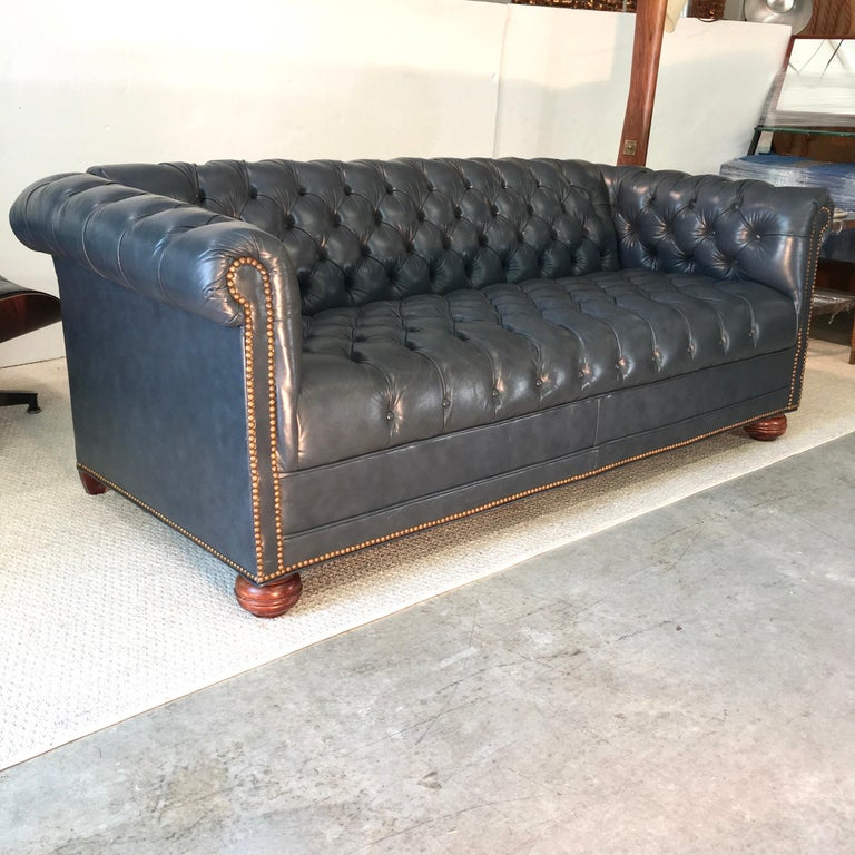 1970s vintage chesterfield sofa in tufted high grade slate blue/gray leather and brass nailhead trim and a fixed tufted seat base. Sits on solid wood bun feet in front and tapered block in the rear. 21 inch seat depth. Very clean and ready to