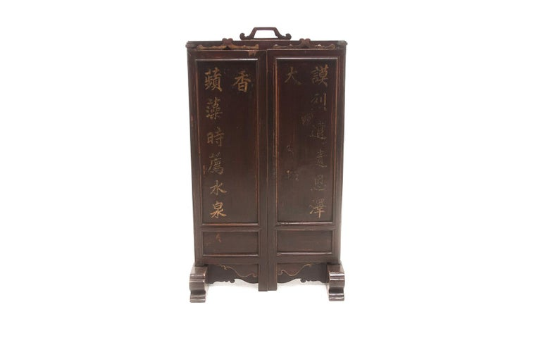 Early 20th century wood and lacquer Chinese ancestral folding table screen with inscriptions  A wood, cast iron lacquered Chinese ancestral folding table screen featuring inscriptions sits on sturdy feet. A wooden carved handle on the top to make