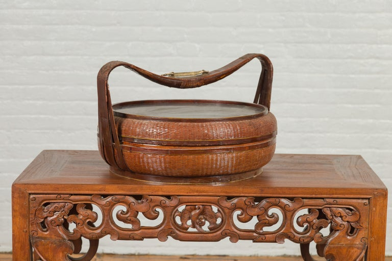 A large Chinese vintage round covered rattan and bamboo basket from the mid 20th century, with hand painted black décor on the top. Crafted in China during the mid-century period, this rattan and bamboo basket was used for storage. Adorned with a