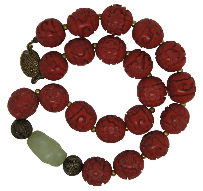 Vintage Chinese necklace of carved red cinnabar beads and a green jade accent bead with silver clasp. Measure: 16