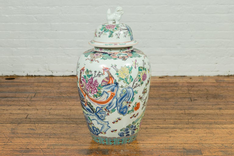 A vintage Chinese palace jar from the mid-20th century, handmade and painted on porcelain and topped with an animal figure. This tall jar features a phoenix among rocks and flowers. This flower and bird theme is common in Chinese painting, but the
