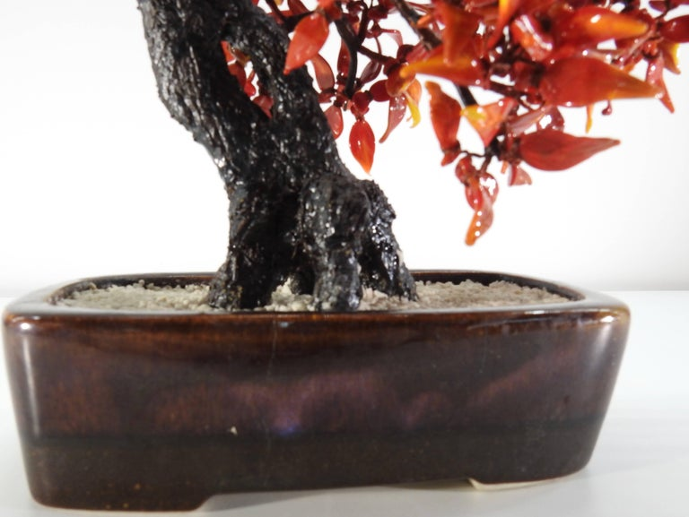 Burnished rust tones of polished glass form the leaves on this Bonsai tree from the 1940s. The branches are neatly covered in silk threads, coming out from the trunk. The tree is planted in a bed of tiny stones which is in a ceramic planter.