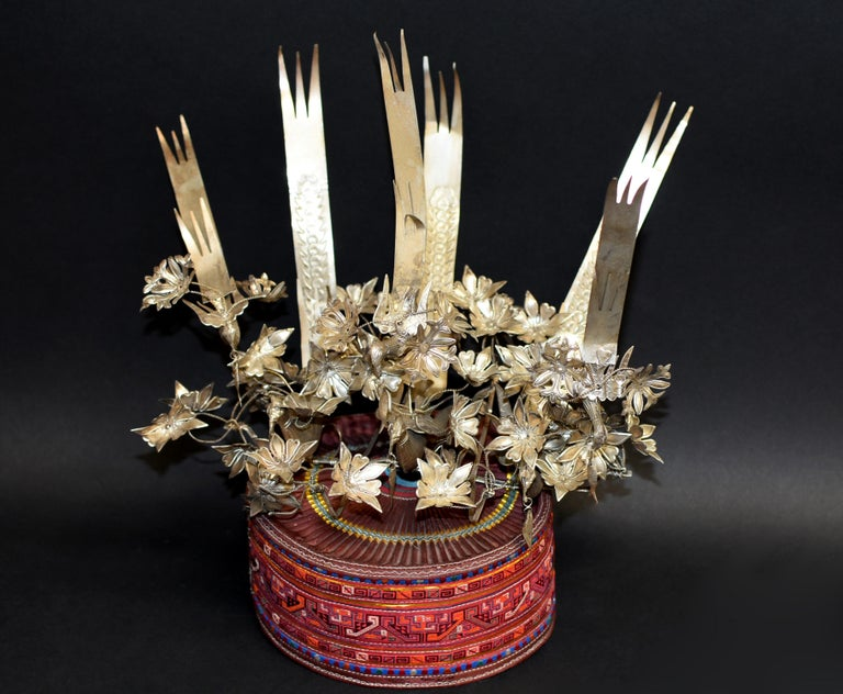 A beautiful hand made Miao tribe hat with silvered metal ornaments. The hand made hat is covered with embroidered bands. The prominent crown is decorated with 6 hand made phoenixes, among which three holding dangling fish in their mouths. The birds