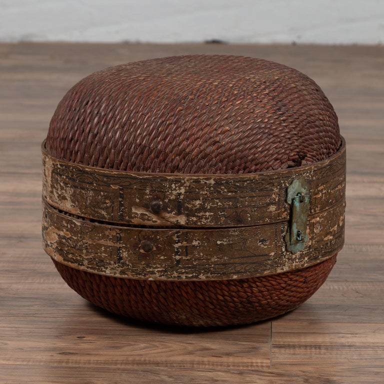 A vintage Chinese rattan hat box from the mid-20th century with weathered patina and oxidized accents. We have similar ones available. Born in China during the midcentury period, this rustic hat box features a rattan body, secured in the middle by