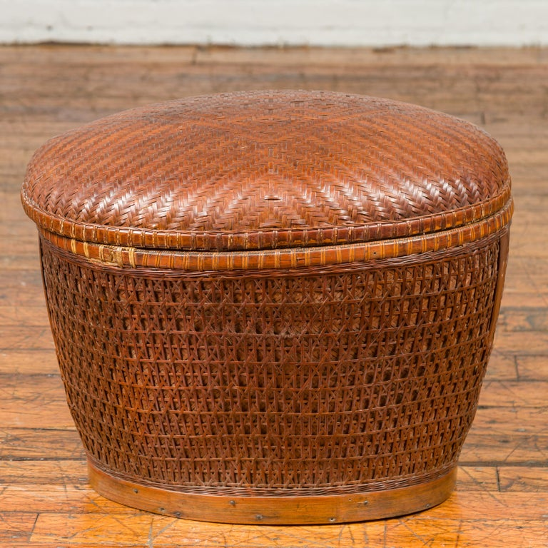 A Chinese vintage unusual oval-shaped rattan basket from the mid-20th century, with lid and geometric motifs. Crafted in China during the midcentury period, this woven rattan basket features an oval uneven lid, adorned with discreet geometrical