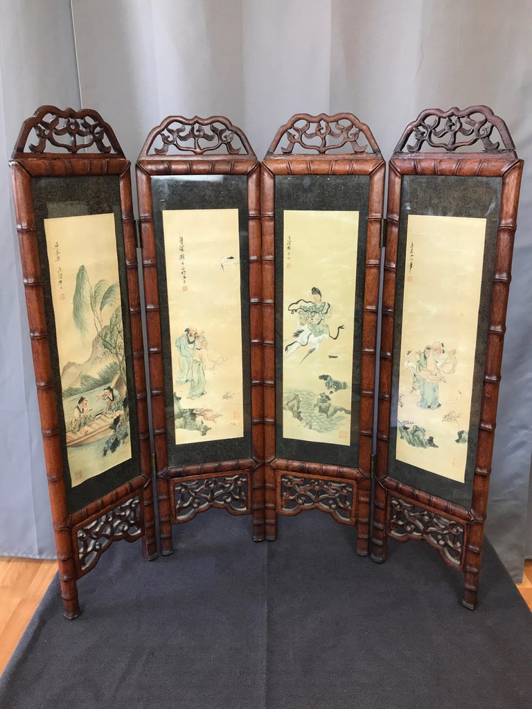 A Chinese Qing dynasty-style mahogany half-size four-panel folding screen featuring a series of original paintings, circa late 1960s.  Finely painted tetraptych on rice paper depicting delightful folkloric vignettes representing luck, prosperity,