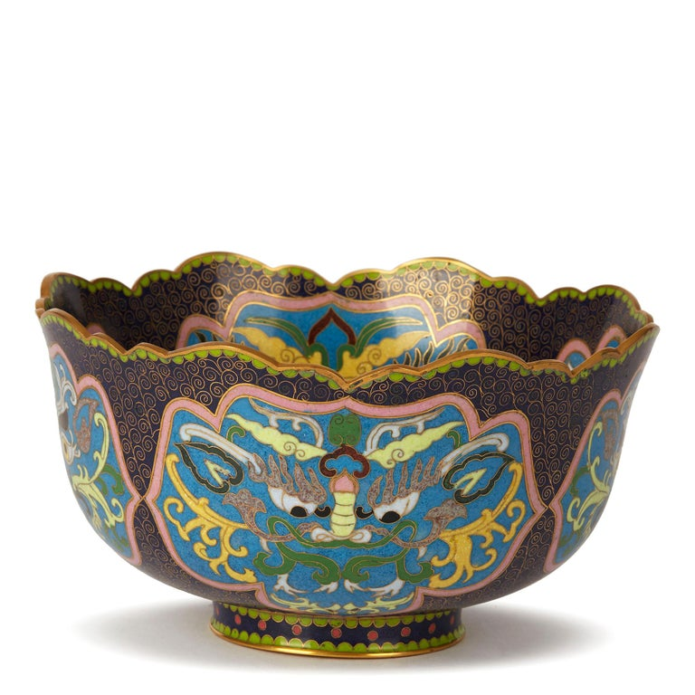 An exceptional and finely decorated vintage Chinese Republic period cloisonné bowl decorated with panels containing grotesque masks. The rounded and heavily made bowl stands on a narrow rounded foot with a shaped rim with a gilded finish to the edge