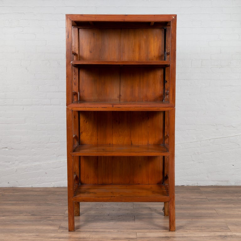 A vintage Chinese two-part elmwood bookcase from the mid-20th century, with pillar-shaped strut motifs and four shelves. Born in China during the mid-century period, this handsome bookcase features a linear silhouette, perfectly complimenting the