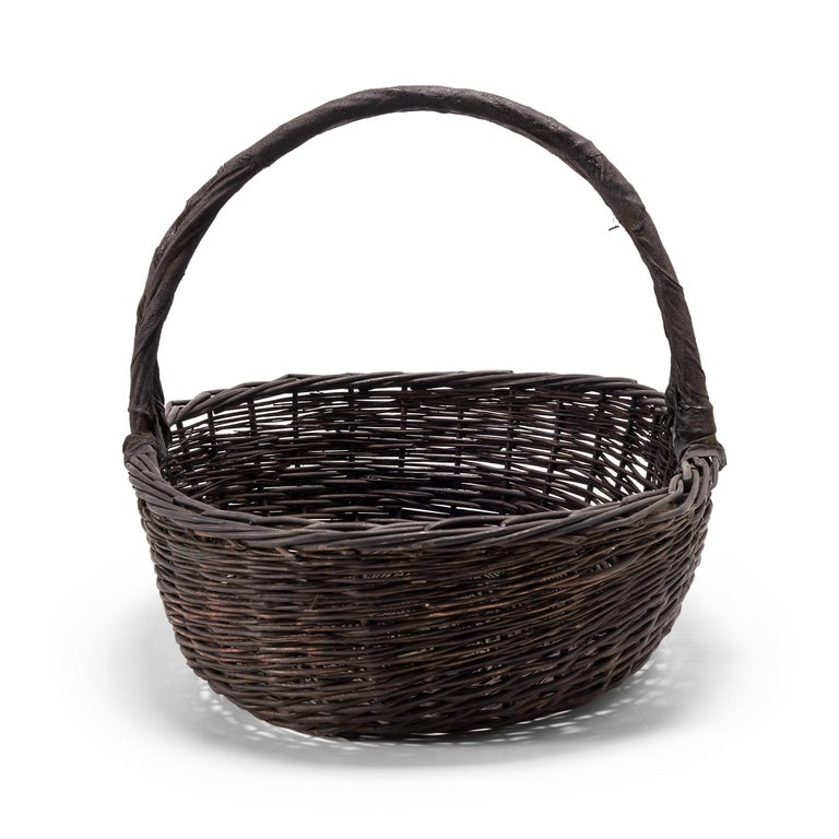 It's easy to imagine the original owner of this basket walking to market on a summer day with the arched handle slung over their arm. Used for carrying food or harvesting vegetables from the garden, this dark, woven basket is a beautiful example of