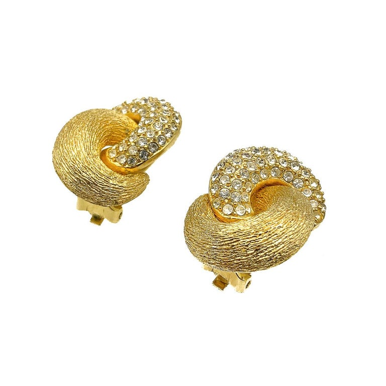 An exceptionally fabulous pair of vintage Dior Crystal Love Knot earrings. Featuring entwined gold loops depicting a love knot. One loop set with crystals for an added touch of glam. Crafted in high quality gold plated metal and crystal stones.