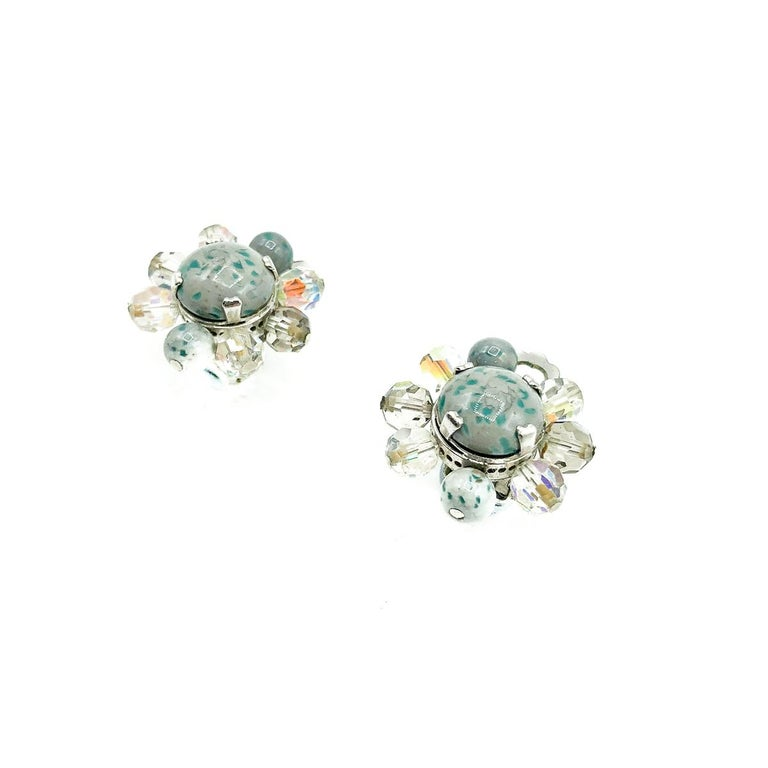 A beautiful and very feminine pair of Vintage Dior Ice Blue Clips from 1958. Crafted with speckled glass cabochon stones in a most fabulous blue grey tone, with aurora borealis crystals set individually with claws and pins. In silver tone metal. In