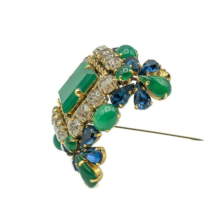 A stunning Vintage Dior Jade Brooch with an outstanding design in three dimensions. Crafted from the most exquisite array of fancy cut glass stones cleverly emulating sapphires, jade and agates and set in gold plated metal. Each stone is claw set.