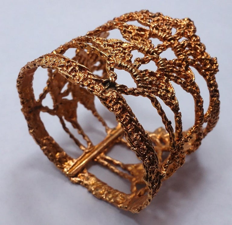 "This vintage signed Christian Lacroix wide cuff bracelet has a heavily intricate openwork design in a gold tone setting.  This cuff measures 3"" x 2-5/8"" and will fit a size 7-1/2"" wrist.  It is signed ""Christian Lacroix Made in France"" and is in"