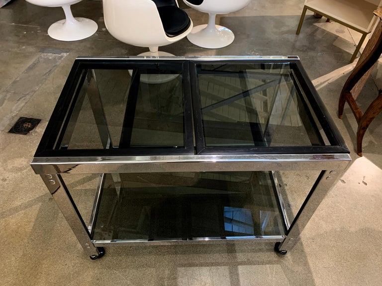 A vintage chrome bar on castors with smoked glass and a slide out top. The top two wood frame tops slide out to make the bar 53 inches wide. It is 36 inches wide when closed. The wood has been repainted at some point black, and there is age