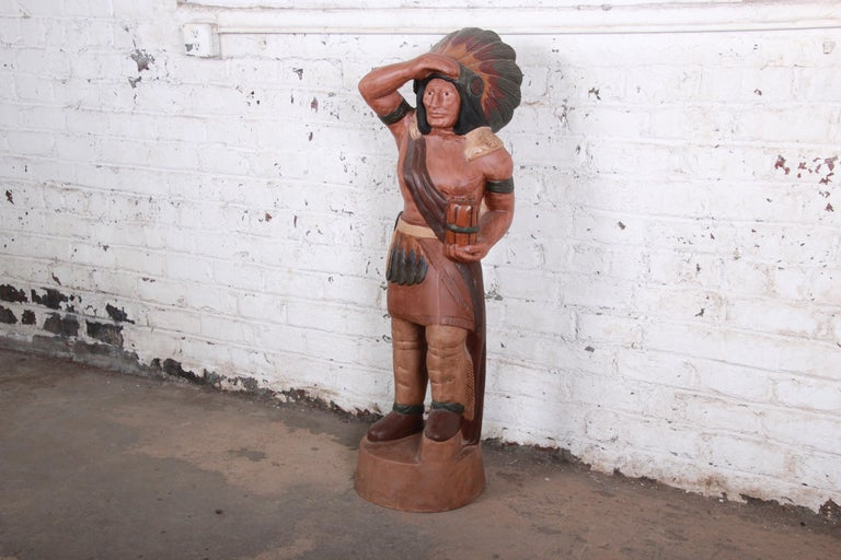An iconic cigar store Indian statue, featuring an Indian chief in traditional headdress. Wonderfully painted in detail over cast metal. The statue is heavy and sturdy. It is in excellent original vintage condition.