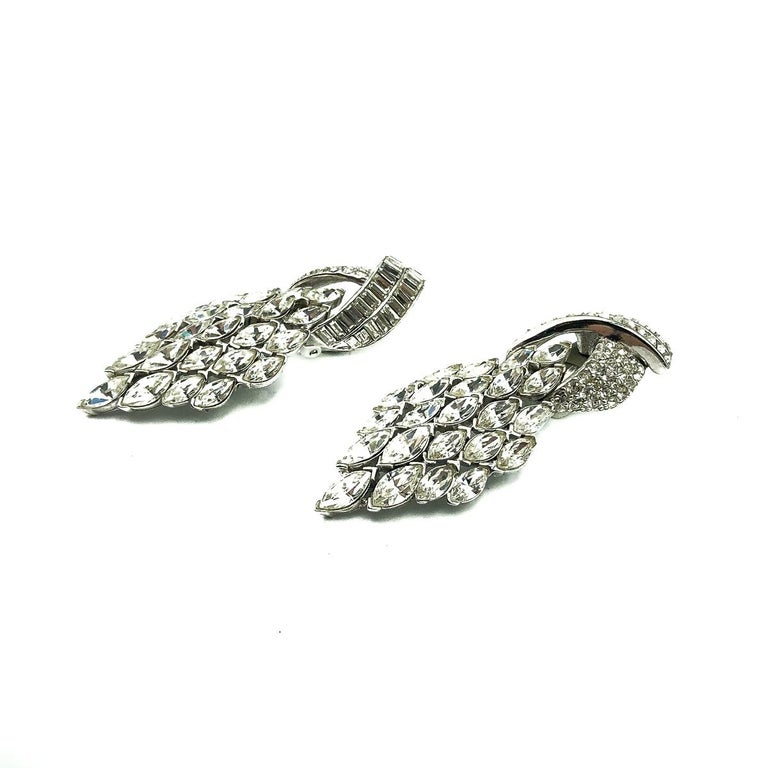 Vintage Ciner Deco Earrings. A captivating pair of Vintage Ciner Art Deco Cocktail Earrings from the 1980s. Adorable, timeless art deco revival earrings encrusted with wall to wall shimmering rhinestones. Crafted in rhodium plated metal. Clip