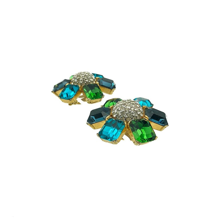 Vintage Ciner Flower Earrings. Crafted in gold plated metal and featuring a sumptuous display of large emerald cut crystals in dark green, deep blue and turquoise. Finished with a central dome of small pave set chatons. Very good vintage condition,