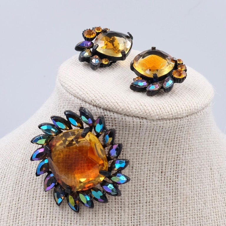 Year: 1950 Hallmark: Claudette Dimensions: brooch H 1.96 in, clip-on earrings D 1.18 in Materials: base metal, glass