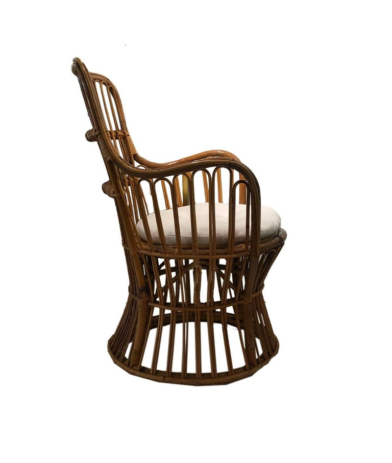 This medium scale rattan chair is a perfect example of its midcentury beginnings. A comfortable seat and new upholstery allow this chair to mix with many styles and become a comfortable place to sit in your home!
