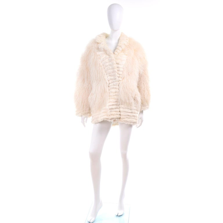 We are in love with this beautiful creamy ivory Tibetan lamb fur coat with rabbit fur trim and ivory silk lining. The jacket closes with fur coat style hooks and has the Maison Blanche and Made in Hong Kong labels.  This beautiful coat has side slit