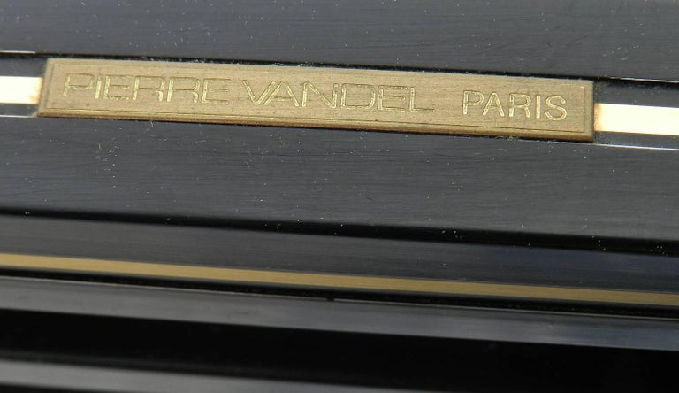 Midcentury coffee table by Pierre Vandel, Paris, France Makers label Black lacquered metal frame with brass trim Beveled glass top Overall good vintage condition minor scattered surface wear to frame, just one corner has slightly more as shown