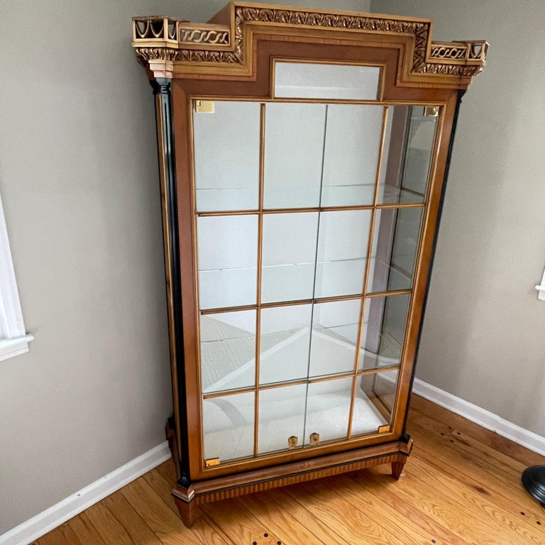 Italian Biedermeier style Colombo mobili display cabinet with internal lighting This large stately cabinet is cherry and yew wood framed with 3 beautiful glass panes framed in wood flanking the front. Glass shelves on the interior. The header is