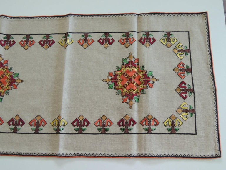Vintage colorful embroidered table runner textile.