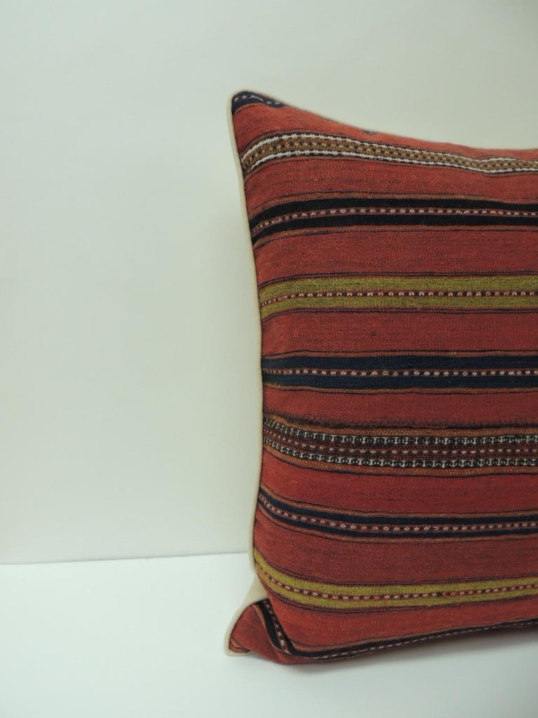Vintage colorful Turkish stripes woven square decorative pillow. Decorative square pillow handcrafted with a woven textile with stripes in shades of green, blue, black, white, yellow and red. Square throw pillow embellished with a small yellow