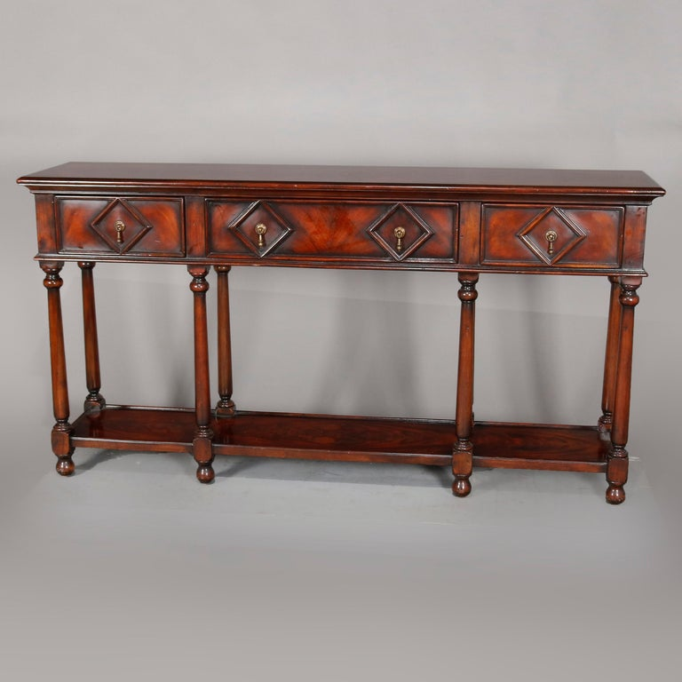 A vintage Continental mahogany silver server offers flame mahogany construction with deeply striated top surmounting case with three drawers, each having geometric diamond reserve, raised on turned legs with lower display shelf, circa