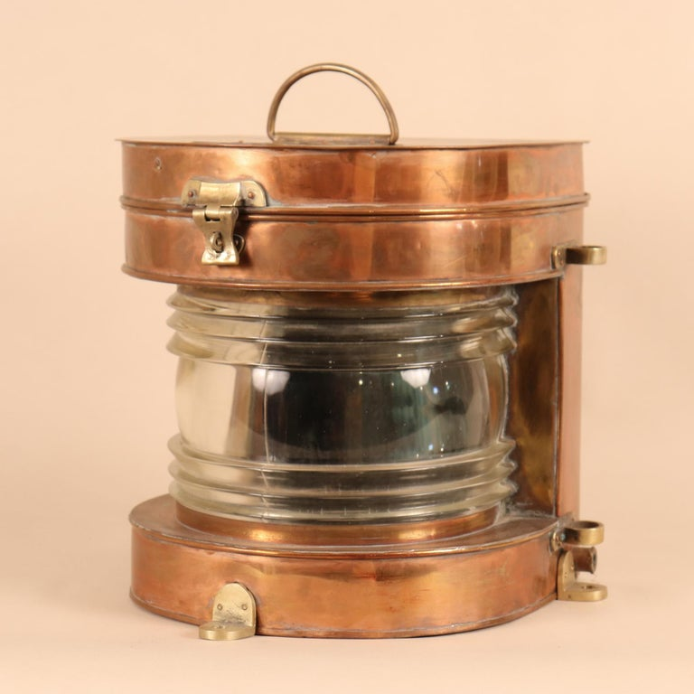 An authentic, vintage copper nautical lantern with brass accents and thick glass Fresnel lens. This circa 1950 marine light, manufactured by Tung Woo, Hong Kong, is hinged and hasped on top so that changing the bulb is easy. The lantern has all of