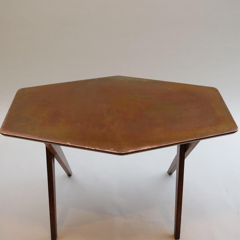 1950s side table made from oak with plywood and copper top. Hand produced in the 1950s. Very nice design with cross over legs and shaped top. In good vintage condition with wonderfully patinated copper; nice color and distressing to the oak