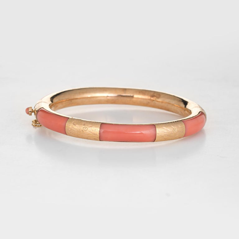 Stylish and finely detailed vintage coral bangle bracelet crafted in 14 karat yellow gold.    Coral is inlaid flush into the bangle and measures 7mm wide. The coral is in excellent condition and free of cracks or chips.    The bracelet makes a nice