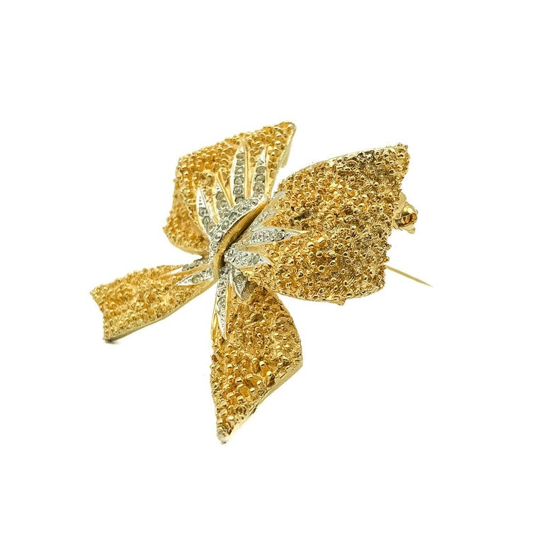 Vintage Corocraft Bow Brooch. Crafted in gold plated metal and crystals. Featuring a large floppy bow design in stippled effect metal with a central crystal spray. In very good vintage condition, signed and approx. 6.5cm. A perfectly timeless pin
