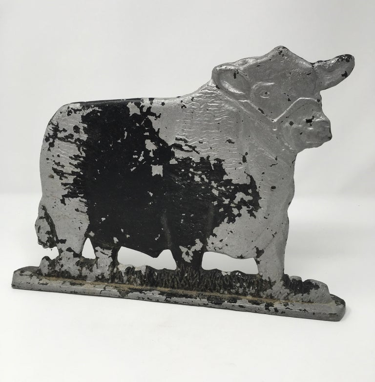 This vintage metal cow was once used as a fence topper on a ranch in Texas. Made of cast iron, with remnants of silver paint, this cow fence topper has nice molded detail and is unmarked by the maker. This piece probably dates to the early 1900s.