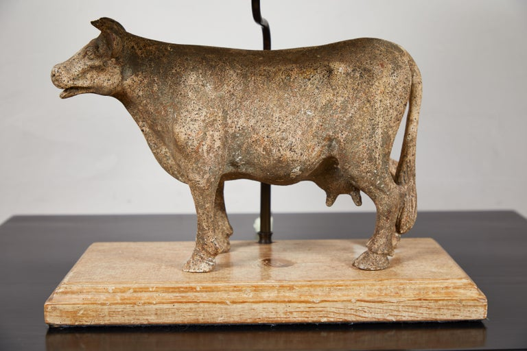Painted plaster cow on wood base with black painted metal shade. Vintage.
