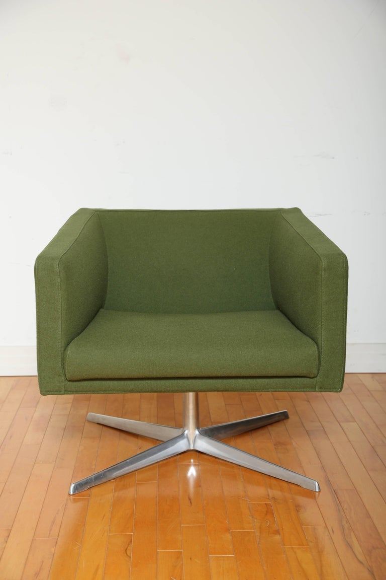 Modernist armchair with cubist form featuring full 360 degree swivel. Streamline design lends itself to both home or office setting. Upholstered in army green wool blend fabric with four legged support base in solid heavy weight polished aluminum,