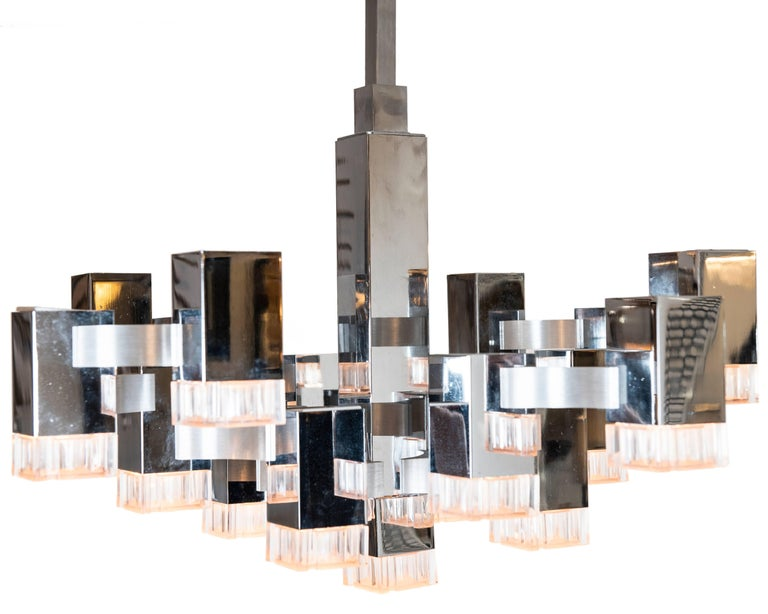 This iconic and cool 17 light Sciolari pendant with chromed metal mounts and acylic shades. It has its original chrome mounting pole and matching canopy. The poles may be removed in order to flush mount the fixture (s) if so desired. The overall