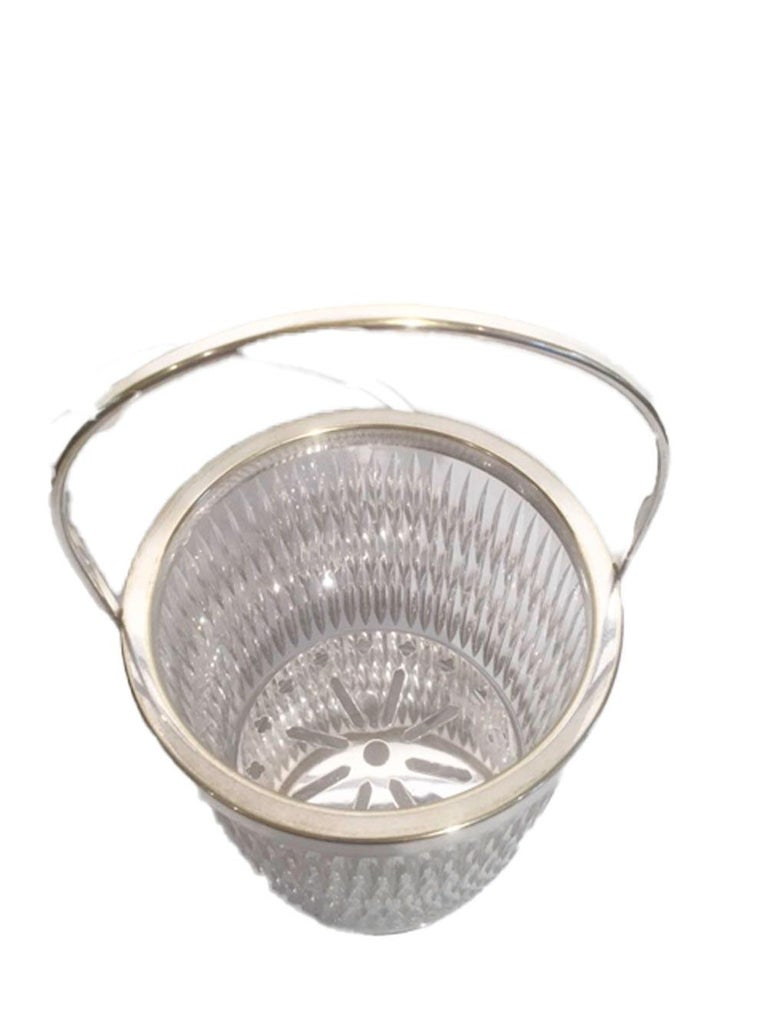Mid 20th century heavy cut glass ice bucket of with silver plate rim and handle. The exterior is cut with three rows of closely spaced vertical lines creating an optical effect above a row of ovoid cuts at the base, the bottom is finished with a
