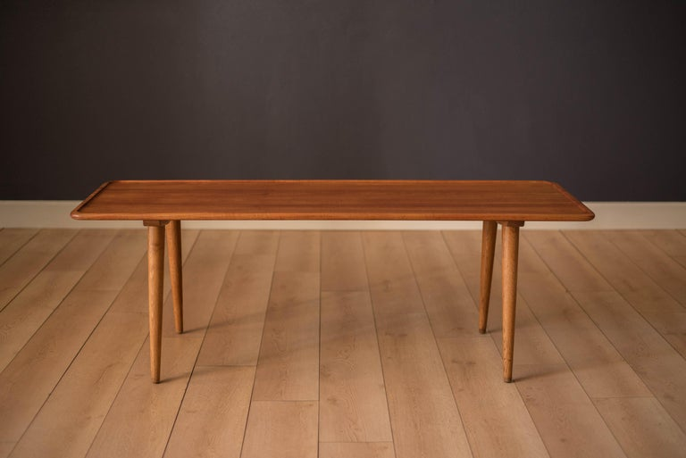 Mid-Century Modern original coffee table designed by Hans Wegner for Andreas Tuck model AT-11. This solid planked teak tabletop displays a sleek Minimalist design with raised rounded edges. Supported by four sturdy oak legs that splay at an angle.