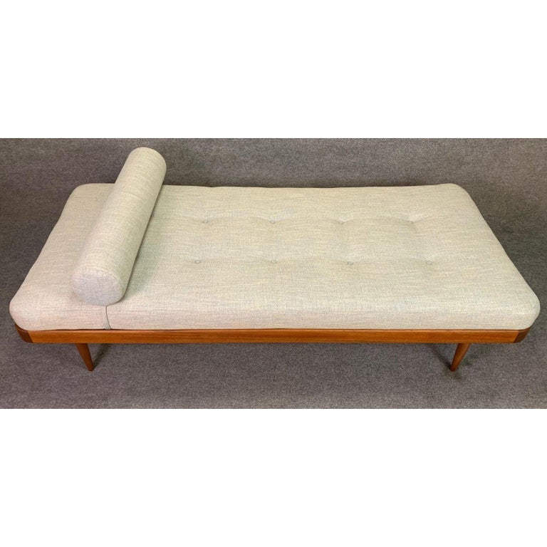 Here's a beautiful Scandinavian Modern daybed with a teak frame that was recently imported from Denmark to California before its restoration. This lovely and comfortable piece features a solid teak frame with solid wood slats and legs and a brand
