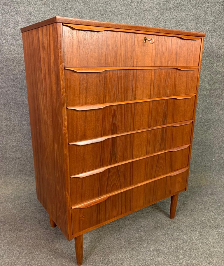 Here is a beautiful 1960s Scandinavian Modern teak highboy dresser recently imported from Denmark to California before its complete refinishing. This exquisite dresser features a vibrant wood grain, six dove tail built drawers (top one with a