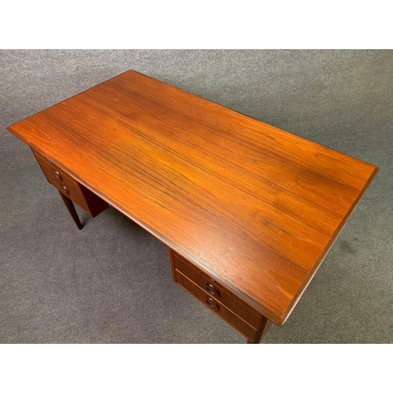 Here is a beautiful Scandinavian Modern teak desk manufactured in Denmark in the 1960s recently imported to California before its restoration. This exquisite desk feature, a vibrant wood grain, a single drawer flanked by two banks of three drawers