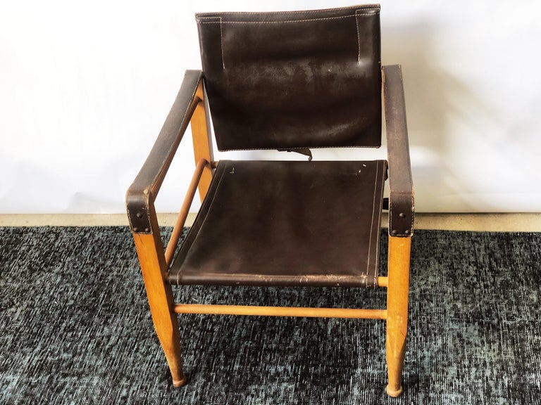 This vintage Danish modern, original leather, and beechwood frame safari chair is in overall good condition. Shows wear consistent with age and use. Lightweight. Maker unknown. circa 1960s. Dimensions: 22.5
