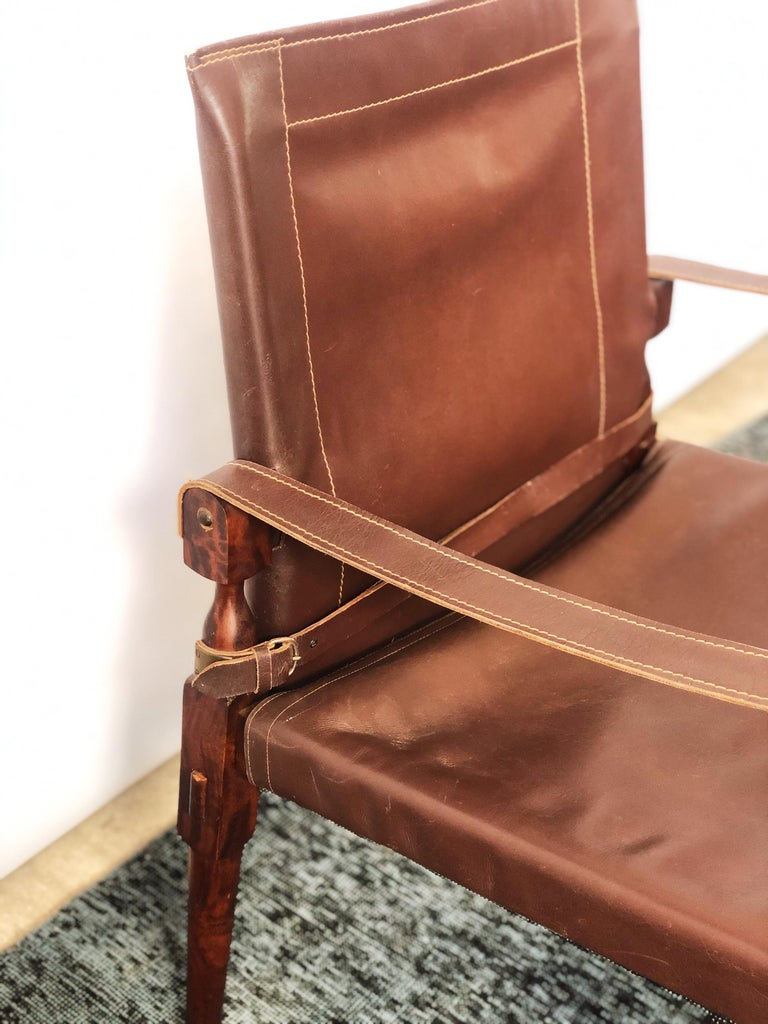 This vintage Danish modern, original leather, and mahogany frame safari chair is overall good condition. Shows wear consistent to age and use. Brass hardware. Lightweight. Maker unknown. circa 1960s. Dimensions: 22