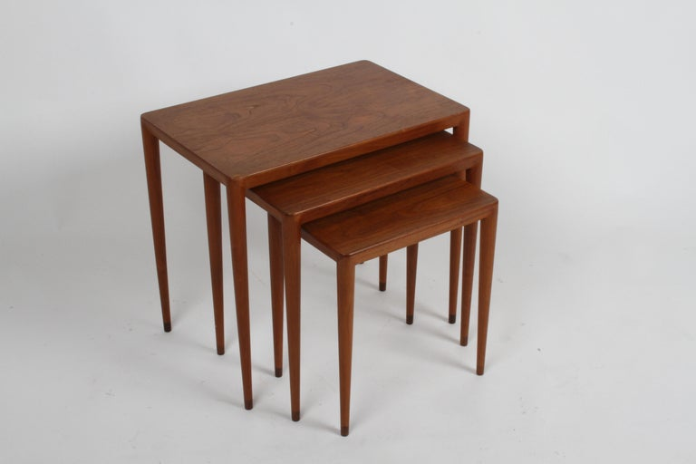 Beautiful set of three teak vintage Danish modern nesting tables with rosewood tips to the tapered legs. Original owner purchased them in the 1960s at the retailer Illums Bolighus in Copenhagen, Denmark. Retains brass label Illums Bolighus