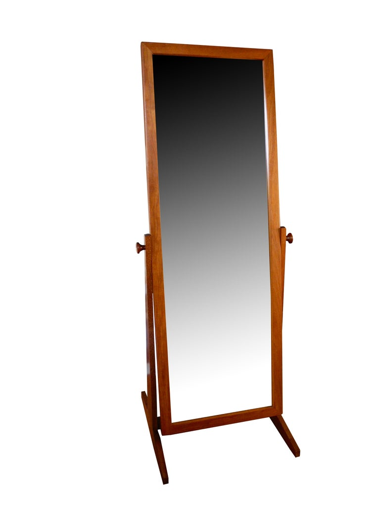 This adjustable 1960s floor mirror stands on its own and is an attractive element in any bedroom or dressing room. Made of teak in Denmark by Pedersen & Hansen. The mirror measures 21 5/8 inches wide by 62 1/2 inches long. The mirror with the footed