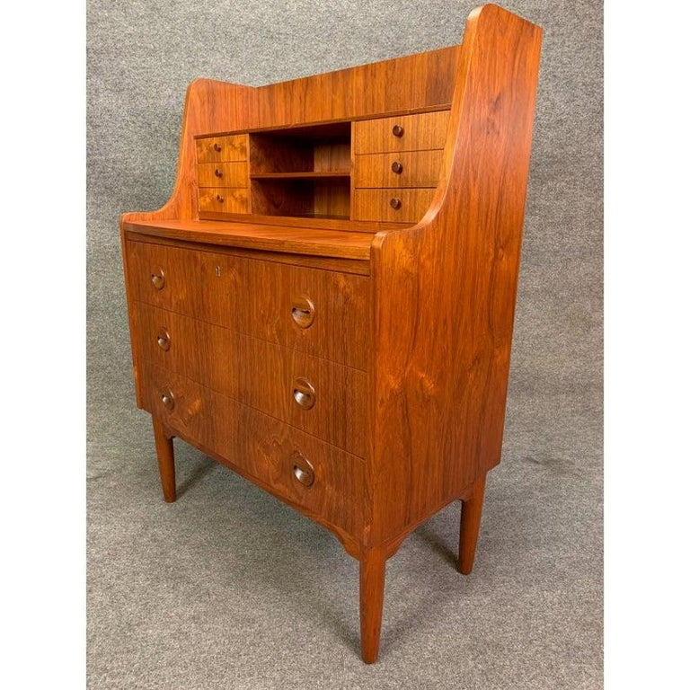 Here is a beautiful 1960s Scandinavian Modern secretary in teak wood recently imported from Denmark to California. This versatile piece, with its vibrant wood grain, features on its top a bookshelf and two mail slots/cubbies flanked by two banks of