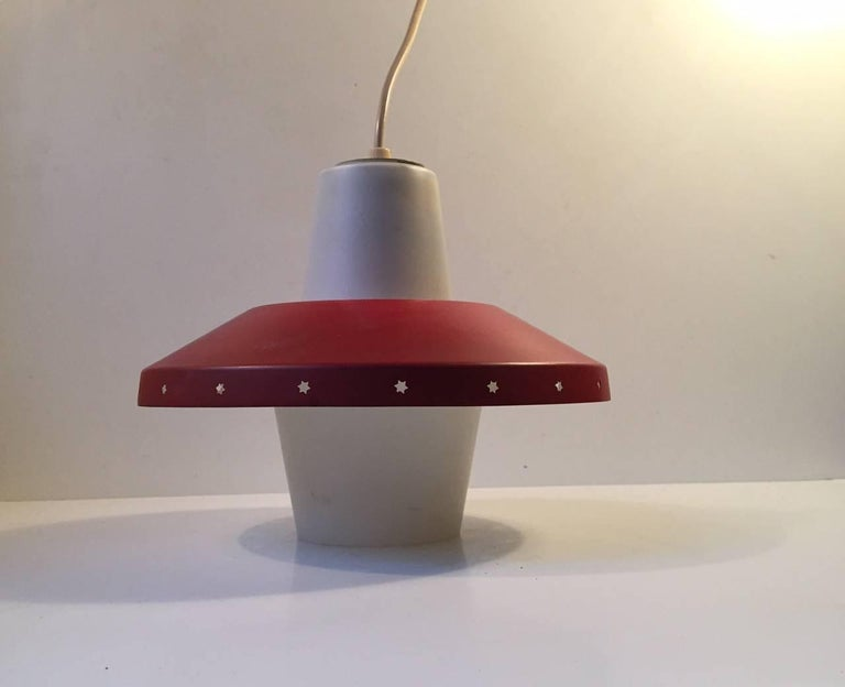 Danish ceiling light designed by Bent Karlby for Lyfa, Denmark and manufactured in the late 1950s. The light consists of red lacquered shade with perforated Stars to the edge and a bell clock shaped opaline glass center. Very nice vintage condition