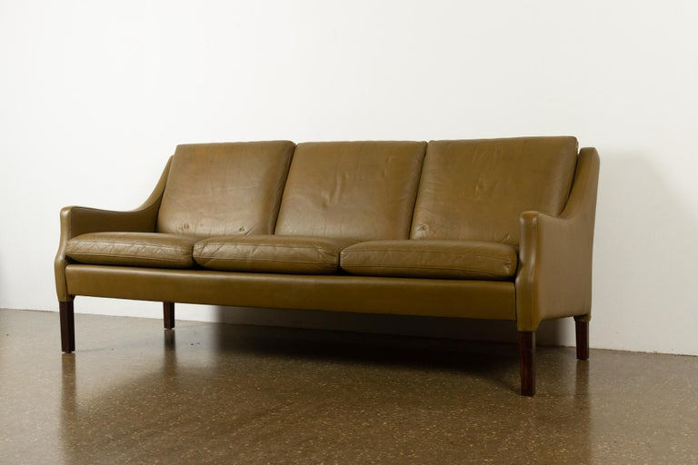 Vintage Danish olive green leather sofa, 1960s Very stylish Mid-Century Modern Danish three-seat couch with original stunning olive green leather upholstery. Beautifully curved armrests. Comfortable with thick and soft seat cushions, leather is