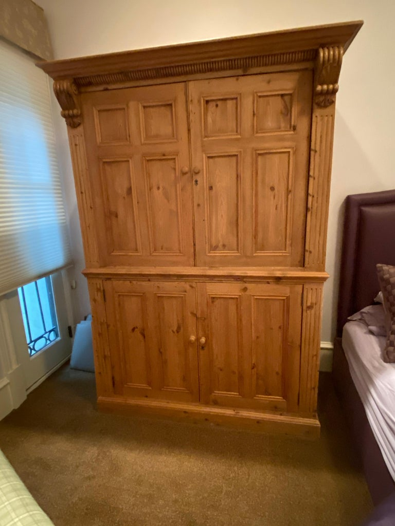 This lovely honey-colored pine armoire from Europe circa 1880, has two doors with recessed panels that are on retractable glides (pocket doors), Comes with working lock & key, with original nickel plates & turned wooden pulls. Provides great storage
